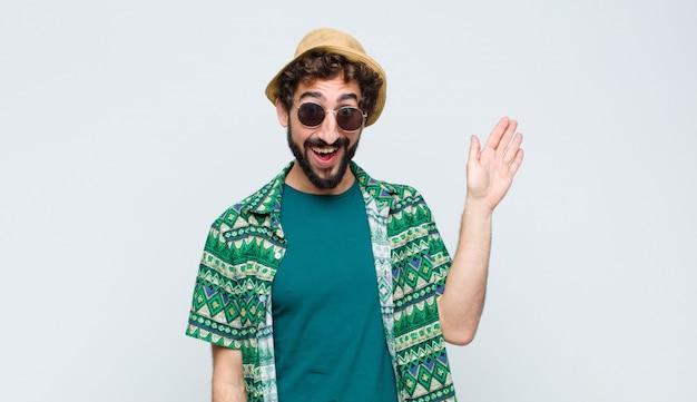 若い観光客の男が幸せそうに笑って、手を振って、歓迎して挨拶するか、白い壁に別れを告げる
