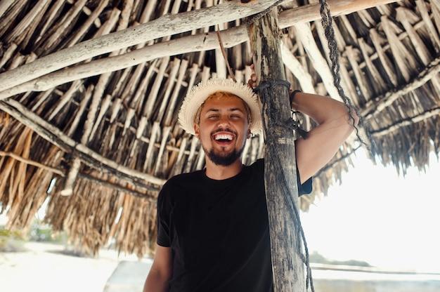 Молодой турист человек улыбается, стоя под бамбуковым зонтиком на пляже