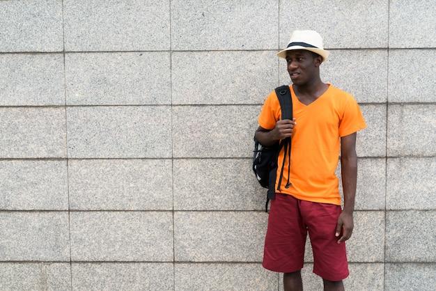 若い観光客男立って、コンクリートブロックの壁にバックパックを押しながら考えて