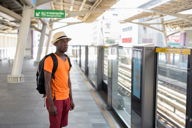 Young tourist man standing and thinking while waiting for the train at bts sky train station of bangkok thailand