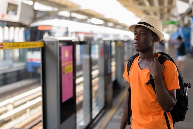 Young tourist man thinking at bts sky train station of bangkok thailand