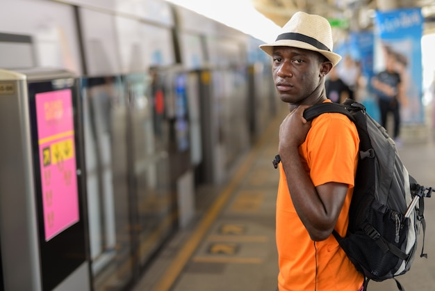 Young tourist man waiting for the train at bts sky train station of bangkok thailand