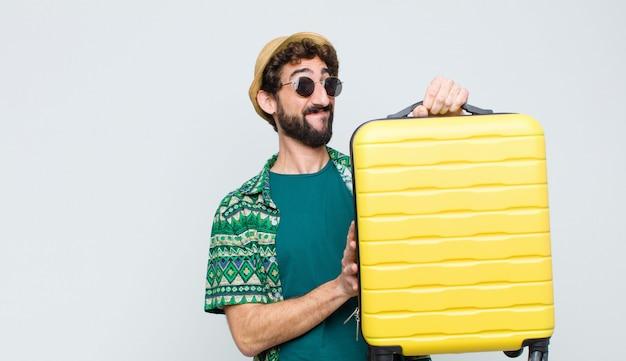 Молодой турист с чемоданом на белой стене