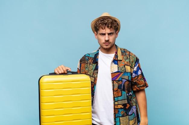 スーツケースを持つ若い観光客の男