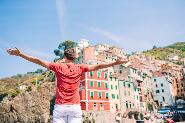 Young tourist man with great view of stunning village of manarola, cinque terre, liguria, italy