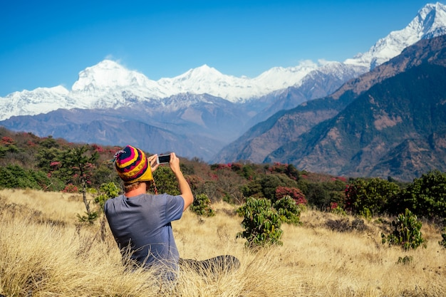 A young tourist man with a hiking backpack and a knitted cap taking pictures of the landscapes and making selfi in the himalaya mountains. trekking concept in the mountains.