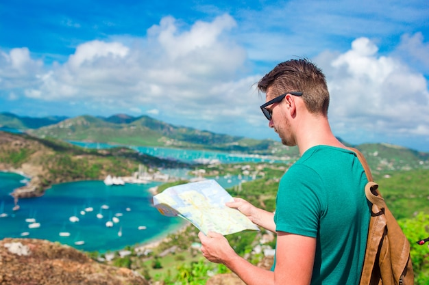 Young tourist man with map of english harbor from shirley heights, antigua, paradise bay at tropical island in the caribbean sea