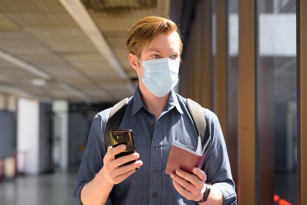 공항에서 생각하는 동안 마스크를 들고 전화와 여권을 가진 젊은 관광 남자