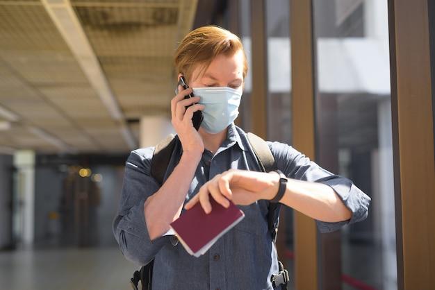 마스크는 전화로 이야기하고 공항에서 시간을 확인하는 젊은 관광 남자