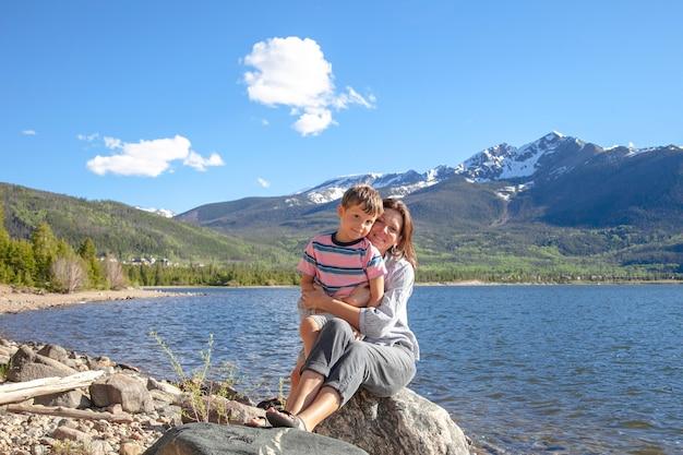 Молодая туристическая мать обнимает сына у озера с прекрасным видом на горы на заднем плане.