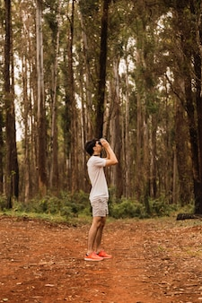 Young tourist observing trees with binoculars. hiker in the jungle looking around.
