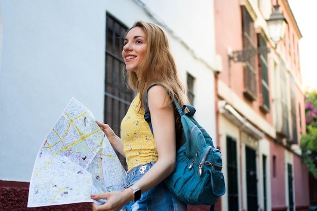 彼女の手に地図を持つ夏休みの若い観光客セビリアの美しい白人女性
