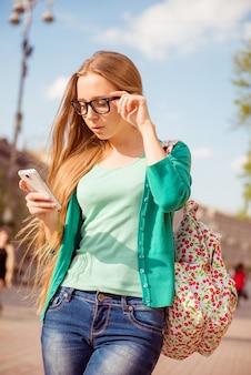 彼女のスマートフォンを使用して方法を見つけようとしている若い観光客