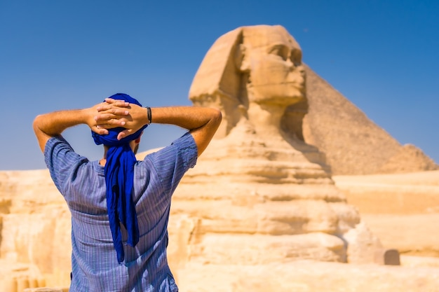 Young tourist wearing a blue turban standing near the great sphinx of giza, cairo, egypt