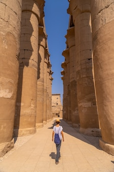 A young tourist wearing a hat visiting the egyptian temple of luxor