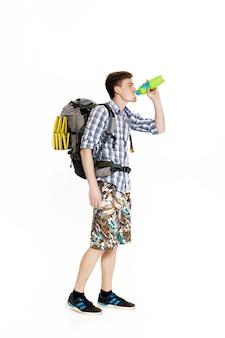Молодой турист с рюкзаком с питьевой водой на белом фоне