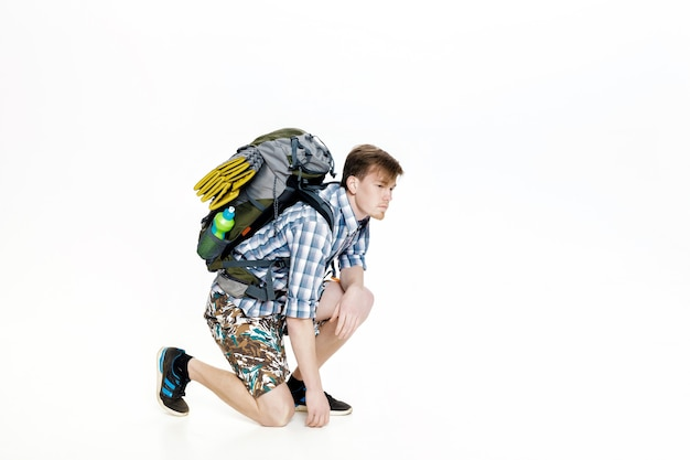 Молодой турист с рюкзаком завязывает шнурки на белом фоне