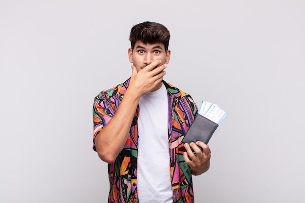 Молодой турист с паспортом прикрывает рот руками с шокированным, удивленным выражением лица, хранит секрет или говорит: упс