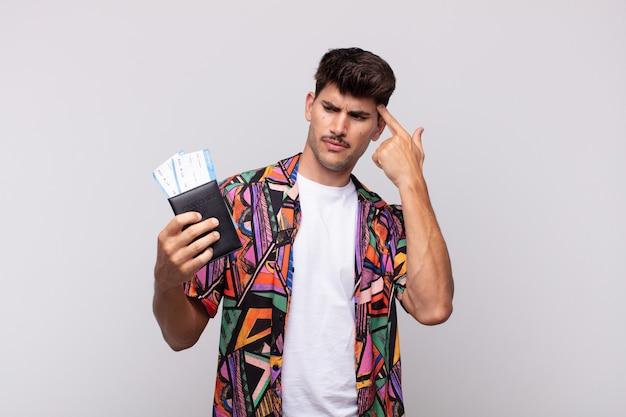 パスポートを持った若い観光客は、あなたが正気でないことを示して、混乱して困惑していると感じています