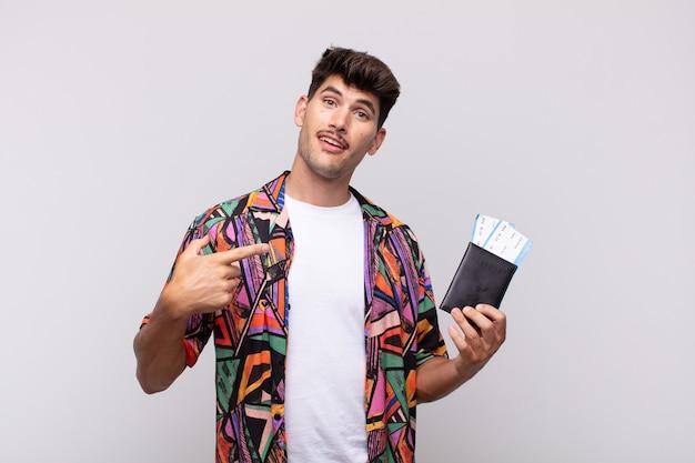 スペースをコピーするために横と上を指している興奮して驚いたように見えるパスポートを持つ若い観光客