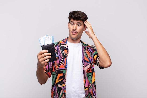 Молодой турист с паспортом выглядит счастливым, удивленным и удивленным, улыбается и понимает удивительные и невероятно хорошие новости