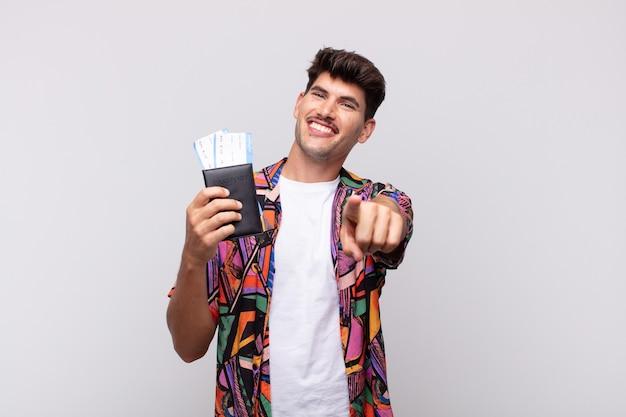 満足のいく、自信を持って、フレンドリーな笑顔でカメラを指しているパスポートを持つ若い観光客、あなたを選ぶ
