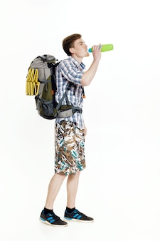 Young tourist with a backpack drinking water on a white background Premium Photo