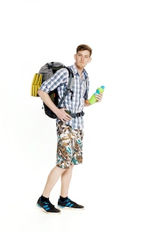 Young tourist with a backpack drinking water on a white background