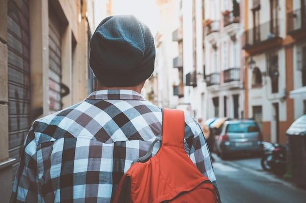 Молодой турист с рюкзаком идет по улице европейского города.