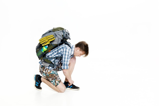 Young tourist with a backpack ties up the shoelaces on a white background