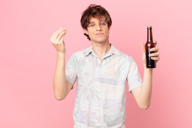 Young tourist with a beer making capice or money gesture telling you to pay