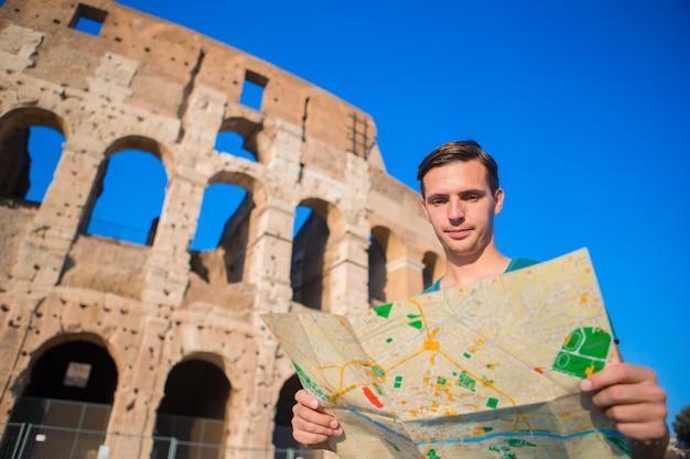 Молодой турист с картой перед колизеем.