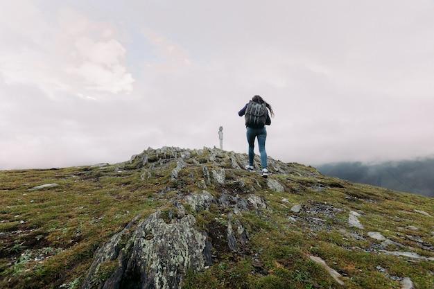 若い観光客の女性は、ジョージア州コーカサス山脈を背景に丘の中腹に双眼鏡に登る