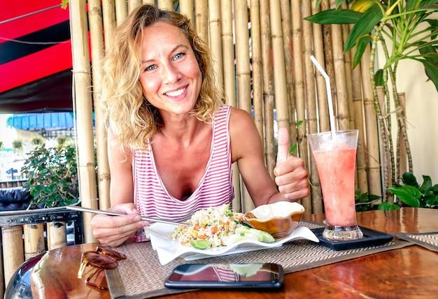 볶음밥을 먹고 태국 푸켓의 태국 레스토랑에서 과일 스무디를 마시는 젊은 관광 여성