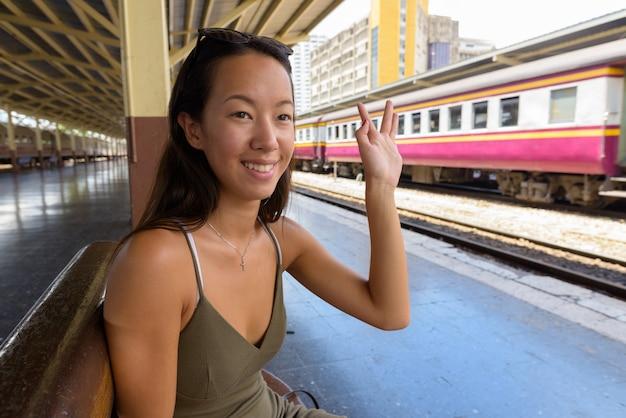 駅でバンコクの街を探索する若い観光客女性