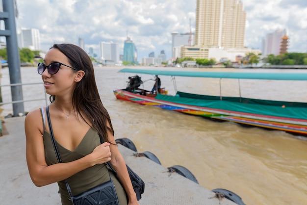Молодая туристическая женщина, изучающая город бангкок у реки