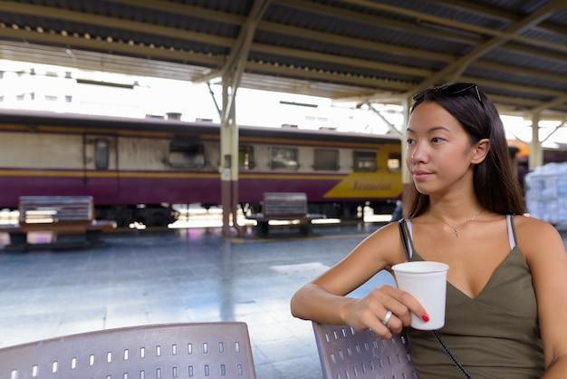 Молодая туристическая женщина, имеющая перерыв на кофе на вокзале