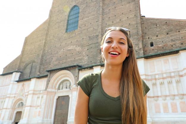 背景にサンペトロニオ教会とボローニャの若い観光客の女性。