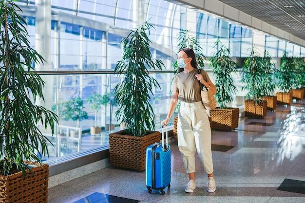 Молодая туристическая женщина в медицинской маске с багажом в международном аэропорту