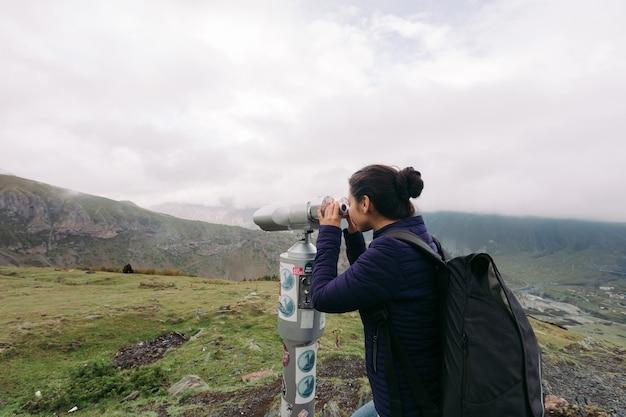 Молодая туристка смотрит в бинокль высокой мощности с монетоприемником на кавказских горах, казбеги, грузия