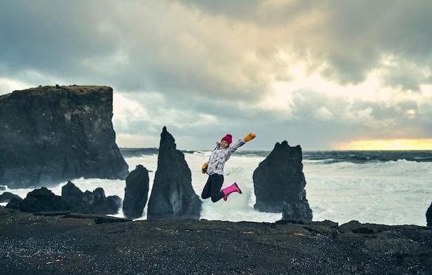 寒い風の強い天候の海岸で帽子と手袋を着用した若い観光客の女性写真家は、岩のある黒い火山玄武岩のビーチに沿って歩きます。