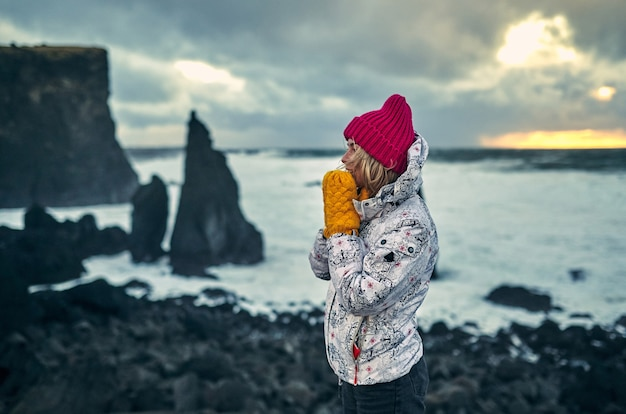 Young tourist woman photographer with hat and gloves on the seashore in cold windy weather, walks along a black volcanic basalt beach with rocks.