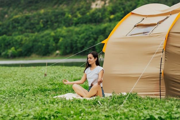 Молодая туристка сидит возле палатки и медитирует. утренняя медитация.