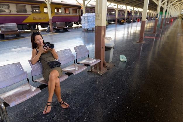 Молодая туристическая женщина сидит и использует камеру dslr