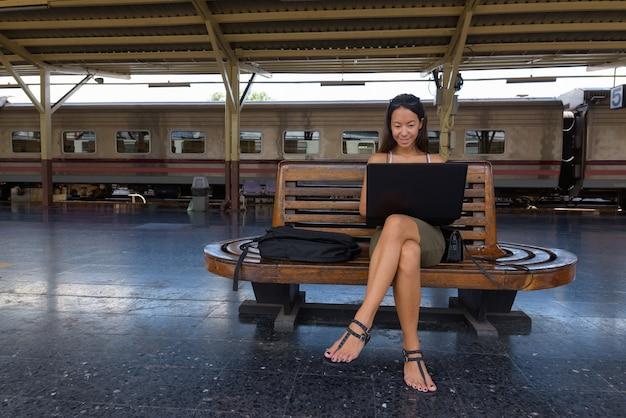 Молодая туристическая женщина сидит и использует портативный компьютер
