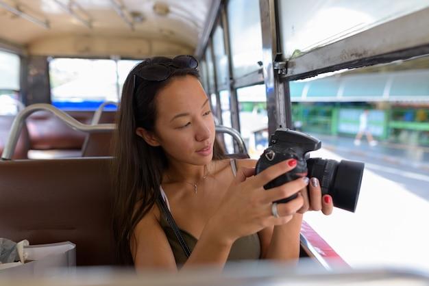 デジタル一眼レフカメラを使用しながらバスに座っている若い観光客女性