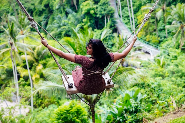Young tourist woman swinging over the tropical rainforest at bali island