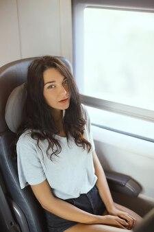 電車の中で座って旅行旅行の若い観光客の女性。ゴージャスな幸せな混血アジアの白人