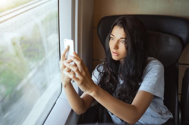 有名な場所の写真を撮る電車に座って旅行旅行の若い観光客の女性。ゴージャス
