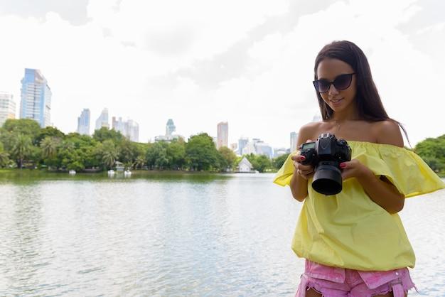Молодая туристическая женщина с помощью камеры в бангкоке, таиланд